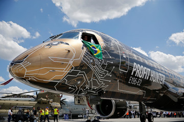An Embraer E195-2 is seen on display, sporting a livery combining a lion's head with an integrated circuit design, during the 53rd International Paris Air Show at Le Bourget Airport near Paris