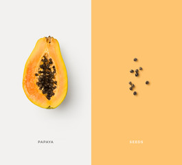 creative food / nutrition / diet concept with colorful isolated papaya half and seeds, minimalist colorful graphic layout