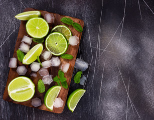Fototapete - Fresh lime, mint and ice on cutting board. Ingredients for Mojito.