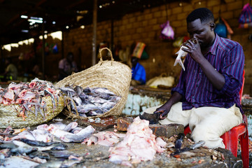 A Sudanese vendor smells a fish to check if it is fresh or not, as he cleans them to sell at a bazaar in Khartoum
