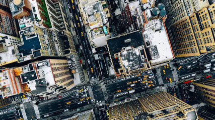 Zelfklevend Fotobehang New York TAXI Aerial view of New York downtown building roofs. Bird's eye view from helicopter of cityscape metropolis infrastructure, traffic cars, yellow cabs moving on city streets and crossing district avenues
