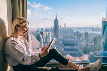 Attractive blonde hair female reading electronic book on digital tablet while sitting on hotel window sill with scenery view of Empire State building and New York downtown. Hipster girl travel blogger