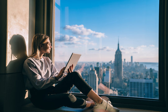 Smiling casual dressed coworking visitor working on freelance with touch pad and enjoying beautiful view of New York city. Caucasian hipster girl enjoying skyline view during vacation holidays in USA