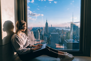 Caucasian female listening to music in headphones while working on laptop computer and enjoying inspiring beautiful view of metropolitan New York city from skyscrapers window. Hipster girl tourist