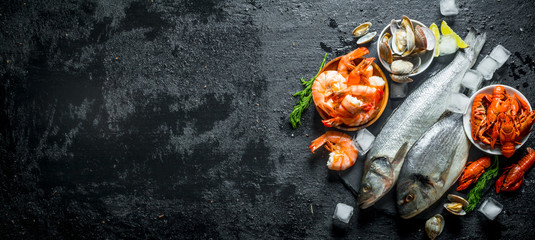 Raw fish and seafood on a stone Board with ice cubes and lime slices. Wall mural