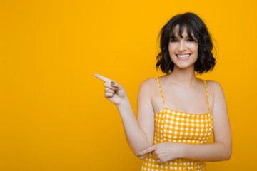 Portrait of a amazing girl with dark short hair pointing awaint with finger laughing dressed in yellow against a yellow background.