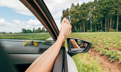 beautiful woman taking picture with a vintage photo camera while relaxing sitting in a car with legs outside the window. holiday, joy, travel, vacation, freedom concept
