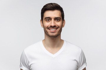 Portrait of smiling handsome young man in white t-shirt looking at camera, isolated on gray background
