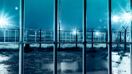 Dramatic Shot Of High Security Prison Facility Yard From Inside Iron Bars During Rain Storm At Night