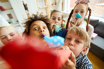 High angle view at multi ethnic group of children blowing party horns at camera and having fun Wall mural