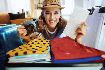 woman with retro film photo camera and map packing for travel