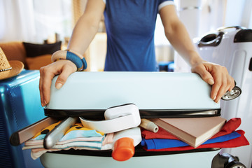 Closeup on traveller woman trying to close over packed suitcase