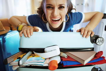 smiling stylish woman trying to close over packed suitcase