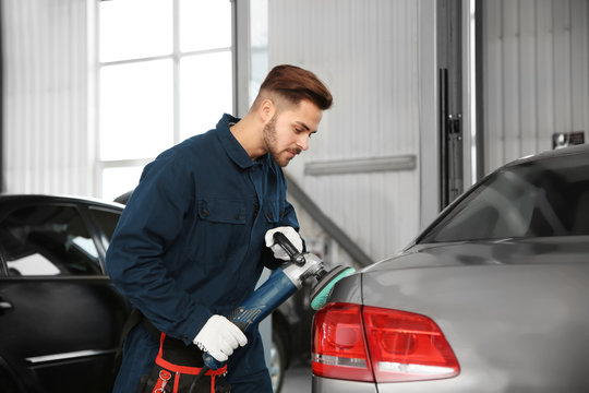Technician polishing car body with tool at automobile repair shop