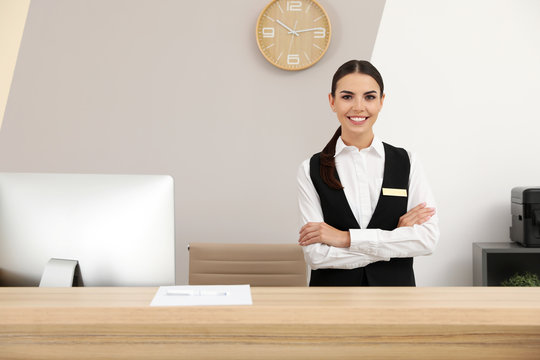 Portrait of receptionist at desk in modern hotel