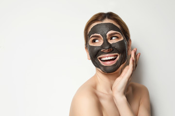 Beautiful woman with black mask on face against light background. Space for text