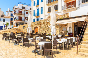 Restaurant tables in port Bo of Calella de Palafrugell, Costa Brava, Catalonia, Spain