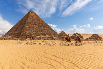 Tuinposter Egypte The Pyramid of Menkaure with three pyramids of the queens and bedouins near them