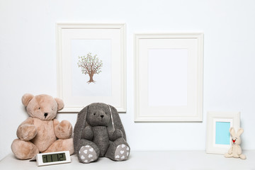 Composition with soft toys and photo frame on white background. Child room interior decor