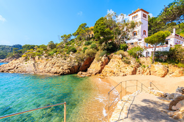 Fototapete - Beautiful beach with small castle on cliff in picturesque Fornells village, Costa Brava, Spain