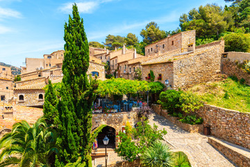 Fototapete - Restaurant in old town of Tossa de Mar with beautiful stone houses, Costa Brava, Spain