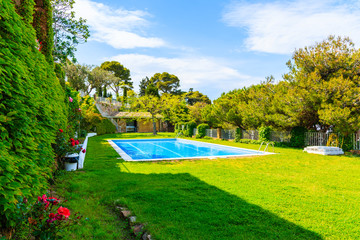TOSSA DE MAR, SPAIN - JUN 3, 2019: Swimming pool in garden of luxury house in Tossa de Mar town, Costa Brava, Spain.