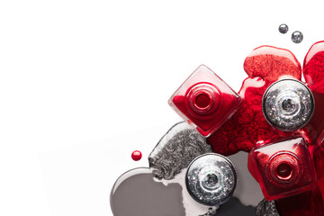Nail art cosmetics concept with red and silver nail polish bottles