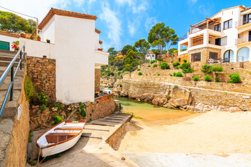 Wall Mural - View of beach with fishing boat and holiday apartments in Fornells village, Costa Brava, Spain