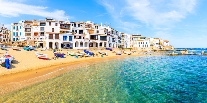 CALELLA DE PALAFRUGELL, SPAIN - JUN 6, 2019: Panorama of amazing beach in scenic fishing village with white houses and sandy beach with clear blue water, Costa Brava, Catalonia, Spain.
