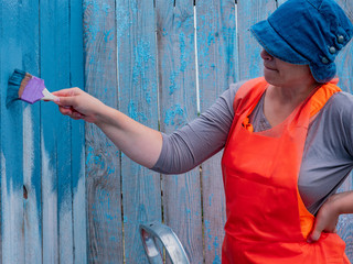 Young Caucasian slim woman in orange clothes and apron paints a wooden fence with a large paint brush  in gray and blue. Paint tank and hands closeup