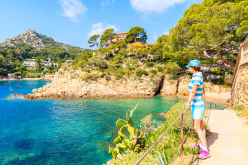 Fototapete - Young woman tourist standing on coastal path and looking at sea in picturesque Fornells village, Costa Brava, Spain