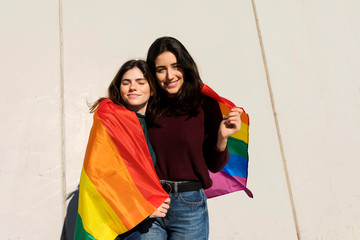 Couple lesbian woman with gay pride flag on the street of Barcel