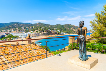 TOSSA DE MAR OLD TOWN, SPAIN - JUN 3, 2019: Statue of Ava Gardner on castle terrace overlooking sea bay of Tossa de Mar. she was an American actress and singer which often was visiting Costa Brava.