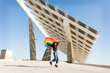 Brunette girl with gay pride flag on a windy  sea view modern Ba