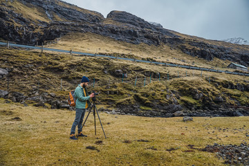 Bearded man in winter clothes using a photo camera on a tripod outdoors in Faroe Islands landscape