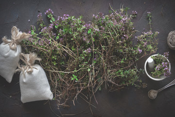 Thyme flowers, mortar and sachets full of thymus serpyllum medicinal herbs. Top view.