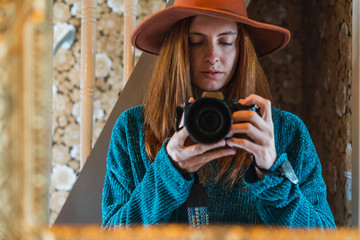 Beautiful young redhead woman in hat taking pictures on professional camera in mirror at home on Faroe Islands