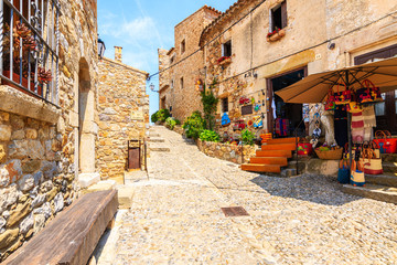 Wall Mural - TOSSA DE MAR OLD TOWN, SPAIN - JUN 3, 2019: Shop with souvenirs and traditional crafts in old town of Tossa de Mar with stone houses, Costa Brava, Spain.