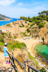 Fototapete - Young woman tourist standing on coastal path and looking at sandy beach and bay in Tossa de Mar town, Costa Brava, Spain