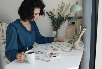 Brunette woman artist sitting at table with cup of coffee and looking at drawings in workplace