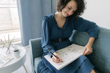 Elegant woman sitting on a sofa drawing flowers on a notebook at home