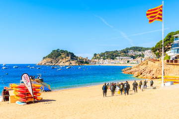 Fototapete - TOSSA DE MAR, SPAIN - JUN 3, 2019: Divers walking to water on beach in Tossa de Mar town, Costa Brava, Spain.