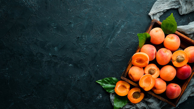 Fresh apricots with green leaves in a box. Rustic style. Top view. Free space for your text.
