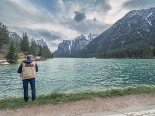 Back view of adult traveler taking photos of mountain ridge while standing on shore of calm lake in nature