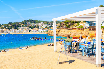 Fototapete - TOSSA DE MAR, SPAIN - JUN 3, 2019: People dining in restaurant on sandy beach in Tossa de Mar town, Costa Brava, Spain.