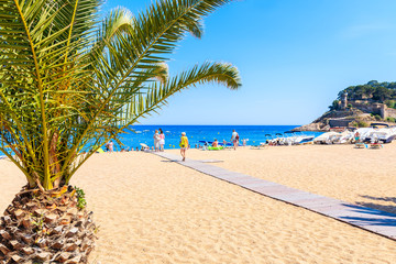 Fototapete - TOSSA DE MAR, SPAIN - JUN 3, 2019: People walking on sandy beach in Tossa de Mar town, Costa Brava, Spain.