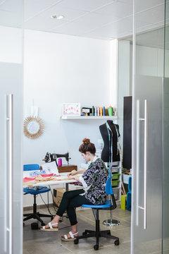 Teenage girl student practicing sewing on modern machine in cozy workshop