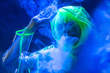 Young pretty unusual Asian woman in plastic transparent raincoat and yellow hair smoking in fluorescent light