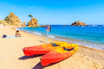 Fototapete - Colorful kayaks on beautiful beach in Tossa de Mar town, Costa Brava, Spain