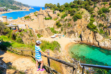 Wall Mural - Young woman tourist standing on coastal path and looking at sandy beach and bay in Tossa de Mar town, Costa Brava, Spain
